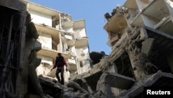 A man stands on a destroyed building after what activists said was an air raid by forces loyal to Syrian President Bashar Al-Assad, in Aleppo's district of Al Sukari Dec. 24, 2013.
