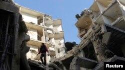 Sebuah gedung di distrik Al Sukari, Aleppo hancur oleh serangan udara pasukan Suriah (24/12).