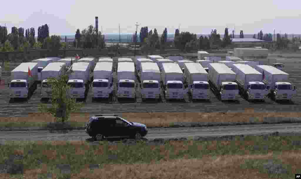 A convoy of white trucks with humanitarian aid parked in a field about 28 kilometers from the Ukrainian border in Rostov-on-Don region, Russia, Aug. 14, 2014.