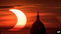 In this photo provided by NASA, a partial solar eclipse is seen as the sun rises to the left of the U.S. Capitol in Washington, June 10, 2021, as seen from Arlington, Virginia.