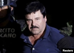 FILE - Recaptured drug lord Joaquin 'El Chapo' Guzman is escorted by soldiers at the hangar belonging to the office of the Attorney General in Mexico City, Mexico Jan. 8, 2016.