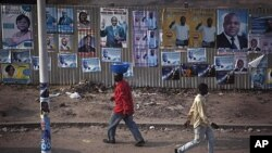 Pedestrians walk past election posters in Democratic Republic of Congo's capital Kinshasa, November 25, 2011.