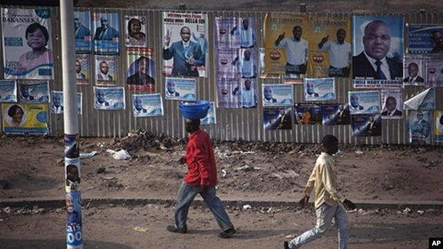Pedestrians walk past election posters in Democratic Republic of Congo's capital Kinshasa, November 25, 2011.