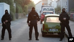 FILE - Special police officers secure a street near the house where a Syrian man lived before the explosion in Ansbach, southern Germany, July 25, 2016.