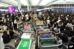 FILE - Protesters use luggage trolleys to block the walkway to the departure gates during a demonstration at the Airport in Hong Kong, Aug. 13, 2019.