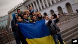 FILE - People holding a Ukrainian flag pose for a photo in Kyiv's Independence Square.
