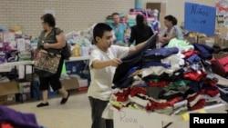 6月27日一名非法移民儿童在德州一个天主教堂设置的临时住所内挑选衣服
