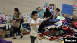 A migrant child chooses clothing at the Sacred Heart Catholic Church temporary migrant shelter in McAllen, Texas, June 27, 2014.