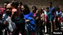 Keluarga migran yang mencari suaka dilepaskan dari tahanan federal di sebuah depot bus di McAllen, Texas, AS, 31 Juli 2019. (Foto: Reuters/Loren Elliott)