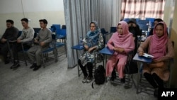 Students attend a class bifurcated by a curtain separating males and females at a private university in Kabul, Afghanistan, Sept. 7, 2021, to follow the Taliban's ruling.
