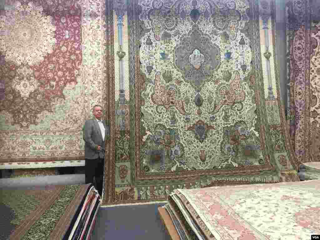 دیوید رستمیان در کنار این فرش که نقشهای تخت جمشید را دارد