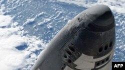 宇航员在空中行走时拍的亚特兰蒂斯号和空间站对接图