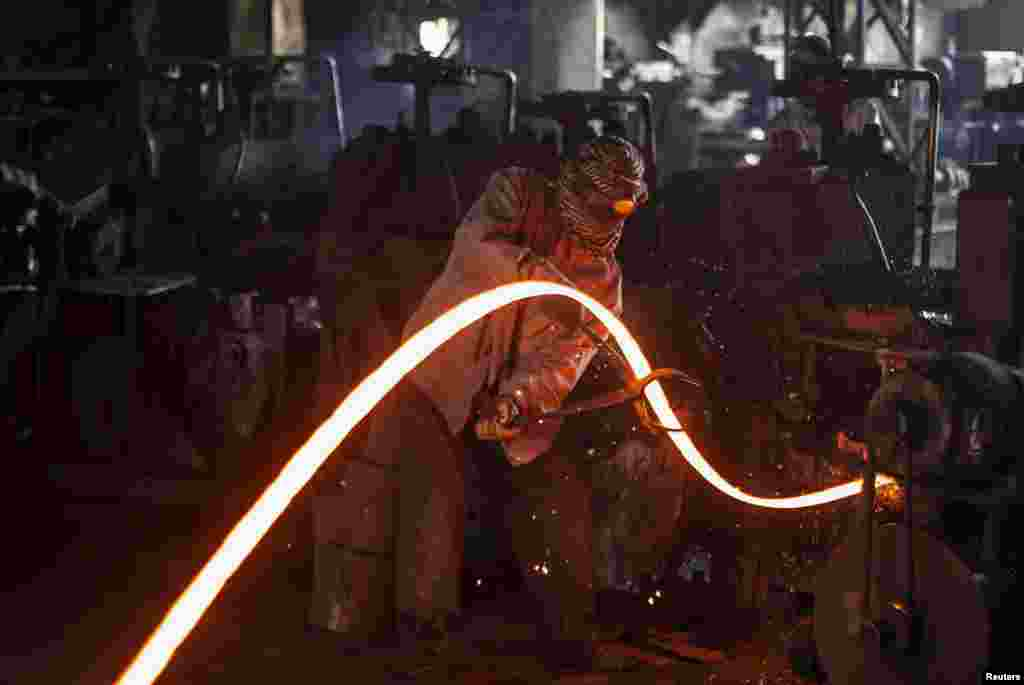 A worker manipulates a hot iron rod at a factory in Islamabad, Pakistan.