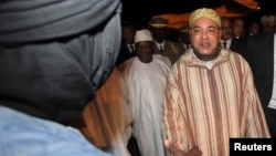 King Mohammed (R) of Morocco greets an unidentified person as he is welcomed by Mali's new President Ibrahim Boubacar Keita (C) at the Bamako-Senou International Airport September 18, 2013. REUTERS/Thierry Gouegnon (MALI - Tags: POLITICS ROYALS) - RTX13QN
