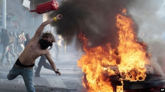 A protestor hurls a canister during clashes in Rome, Saturday, Oct. 15, 2011. Protesters smashed the windows of shops in Rome and torched a car as violence broke out during a demonstration in the Italian capital.