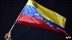 Un hombre muestra una bandera venezolana durante una protesta en Guiria, Venezuela, el 18 de diciembre de 2020.