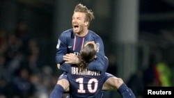 Paris Saint-Germain's Zlatan Ibrahimovic and David Beckham celebrate at the end of their team's French Ligue 1 soccer match against Olympique Lyon in Lyon May 12, 2013.
