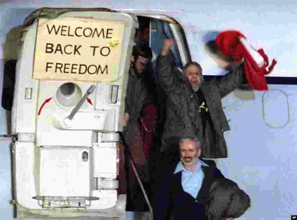 David Roeder shouts and waves as he arrives at Rhein-Main U.S. Air Force base in Frankfurt, West Germany from Algeria on January 21, 1981. He was among 52 Americans held hostage in Iran for 444 days after their capture at the U.S. Embassy in Tehran. (AP Photo)