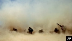 FILE - U.S. soldiers and their Afghan translators shelter from dust kicked up by a Chinook helicopter as it takes off from Mangal Khan village, Khakeran Valley, Zabul province, Afghanistan, June 2005.