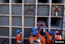 Workers place the coffin of a mudslide victim into a grave at the cemetery in Santa Catarina Pinula, on the outskirts of Guatemala City, Oct. 6, 2015.