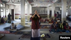 A Tibetan woman offers prayer upon her arrival to an event organized to express solidarity with the victims of violence in Tibet and to those who self-immolated to protest against Chinese rule in Tibet, in Kathmandu, November 17, 2012.