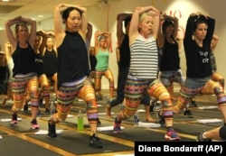 Women wear leggings while practicing yoga.