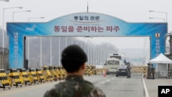 South Korean soldiers stand as vehicles carrying a South Korean delegation pass the Unification Bridge, which leads to the Panmunjom in the Demilitarized Zone in Paju, South Korea, Thursday, March 29, 2018. (AP Photo/Lee Jin-man)