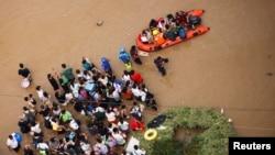 Warga yang terdampak banjir di Zhengzhou, provinsi Henan, China, menunggu untuk dievakuasi, 22 Juli 2021. (REUTERS/Aly Song)