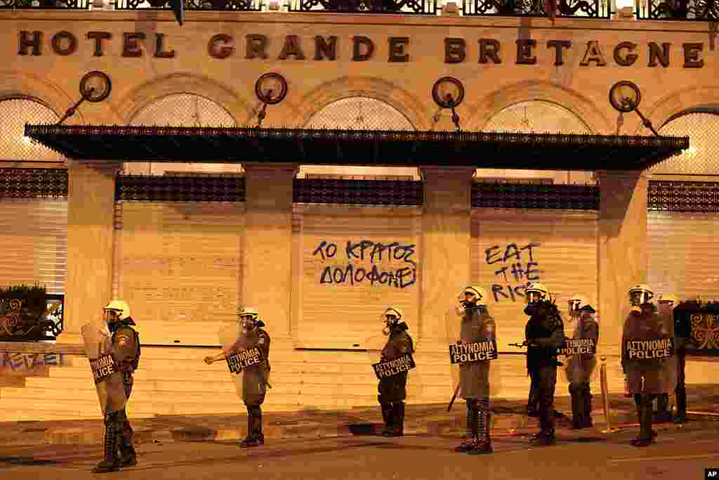 Riot police secure the area outside a shuttered luxury hotel where graffiti reads ''the state murders.'' (AP)