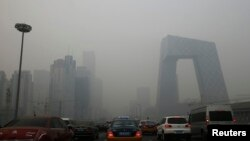Cars travel on a road amid heavy haze in Beijing, Feb. 21, 2014.