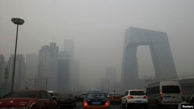 Cars travel on a road amid heavy haze in Beijing, Feb. 21, 2014.