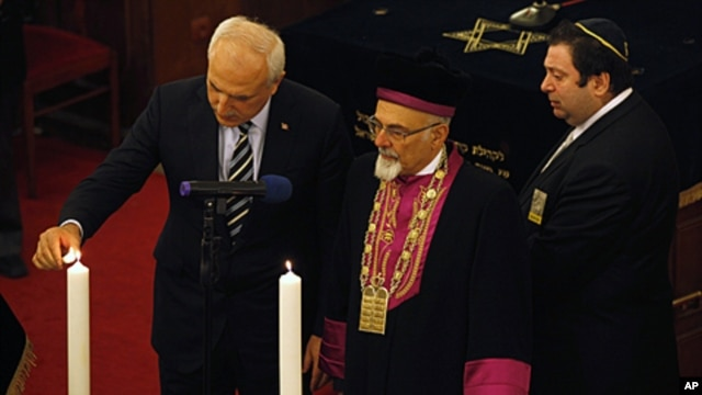 Turkey's Chief Rabbi Izak Haleva (C) and Istanbul Governor Huseyin Avni Mutlu (L) light candles, in memory of holocaust victims, during a commemoration to mark International Holocaust Remembrance Day at Neve Shalom Synagogue in Istanbul, January 26, 2012.