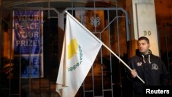 An anti-Troika protester holds a Cypriot flag during a demonstration outside the EU offices in Nicosia Mar. 24, 2013.