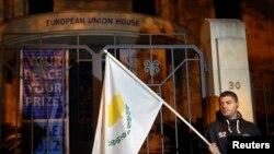 3月24日一名塞浦路斯抗议者在尼科西亚的欧盟办公室外手持塞浦路斯国旗示威