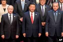 Chinese President Xi Jinping (center) stands with Russian President Vladimir Putin (left) Turkish President Recep Tayyip Erdogan (right) and other leaders to pose for a group photo before the opening ceremony of the Belt and Road Forum.