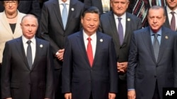 Chinese President Xi Jinping (center) stands with Russian President Vladimir Putin (left) Turkish President Recep Tayyip Erdogan (right) and other leaders to pose for a group photo before the opening ceremony of the Belt and Road Forum the China National Convention Center in Beijing, May 14, 2017.