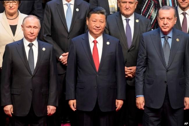 """中国国家主席习近平(中)与俄罗斯总统普京(左)土耳其总统埃尔多安(右)及其他国领导人在北京""""一带一路""""国际合作高峰论坛开幕式上合影。"""
