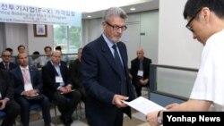 차기전투기사업(F-X) 가격입찰에 참가한 업체 관계자가 18일 한국 서울 방위사업청에서 보안서약서를 전달하고 있다.