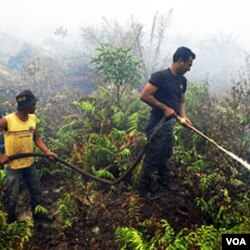 Petugas memadamkan kebaran hutan di Bengkalis, Riau (Oktober 2010). Indonesia sepakat menghentikan pembakaran hutan dan mengurangi emisi rumah kaca.