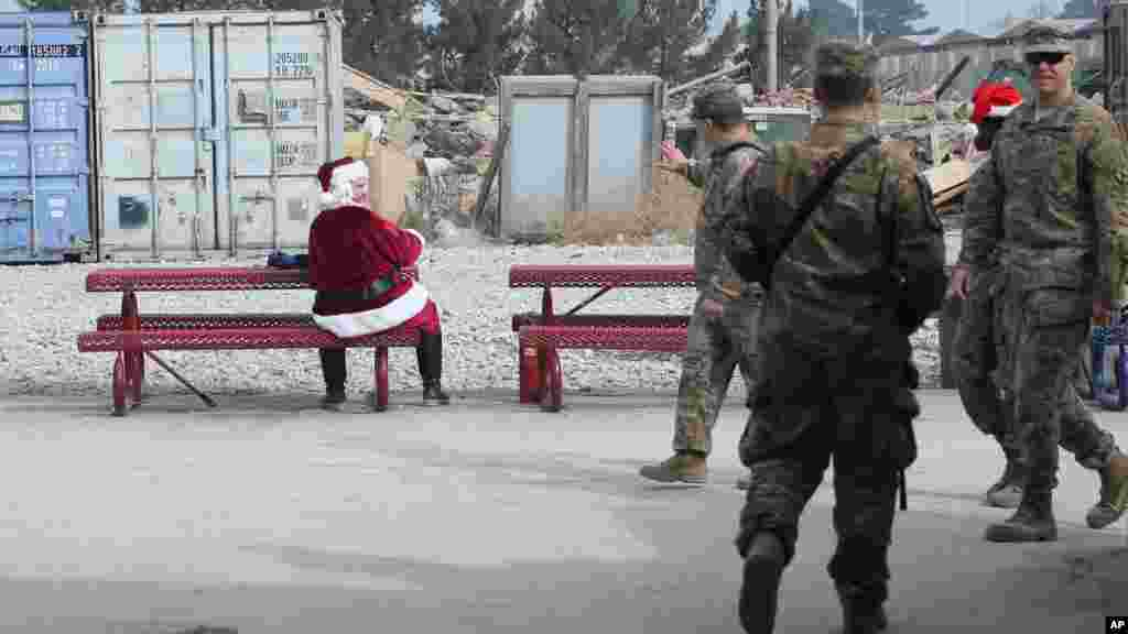 A U.S. soldier dressed as Santa Claus waves to fellow troop son Christmas day at the U.S. air base in Bagram, north of Kabul, Afghanistan, Dec. 25, 2015.