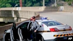 ARCHIVO - Un patrullero estatal de Pennsylvania junto a su vehículo a la entrada de la rampa que conduce a la autopista interestatal 376 saliendo de Pittsburgh. Junio 26, 2018.