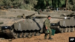 FILE - An Israeli soldier walks past tanks near the Israel and Gaza border, July 10, 2014.