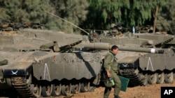 一名以色列士兵行走在停靠在以色列和加沙边界附近的坦克旁。(资料照片)