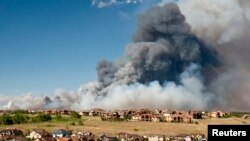 Gumpalan besar asap dari kebakaran di Black Forest membumbung ke angkasa, mengancam rumah-rumah di sebelah utara timur Colorado Springs, Colorado (11/6). Sedikitnya 90 rumah dilaporkan musnah terbakar, dan 7.000 warga terpaksa meninggalkan rumah mereka dalam musibah ini.