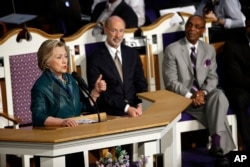 Pennsylvania Gov. Tom Wolf, center, and Pastor James Hall Jr. listen to Democratic presidential candidate Hillary Clinton speak at Triumph Baptist Church in Philadelphia, April 24, 2016.