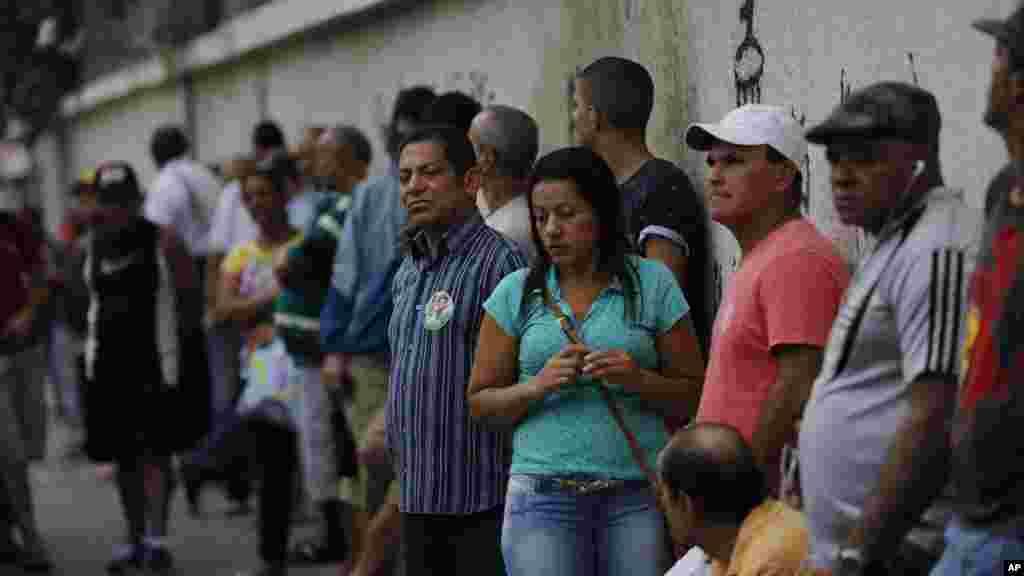 Cientos de brasileños esperan la apertura de las urnas en una escuela de Río de Janeiro, para participar de las elecciones presidenciales.