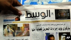 FILE - A man picks up a copy of Al Wasat newspaper at a news stand in Hamad Town, Bahrain, on Tuesday, April 5, 2011.
