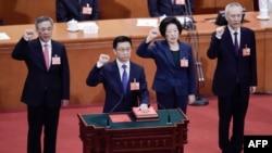 Les vice-Premiers ministres Hu Chunhua, à gauche, Sun Chunlan (2e à droite) et Liu He (à droite), nouvellement élus, prêtent serment au Grand Palais du Peuple, à Pékin, le 19 mars 2018.