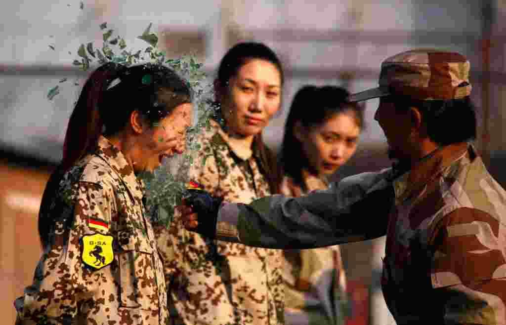 Un instructor de la guardia especial china, rompe una botella en la cabeza de una recluta durante una sesión de entrenamiento de las primeras mujeres guardaespaldas en Beijing, China, 13 de enero de 2012.