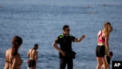 A police officer asks people to not sit while patrolling at the beach in Barcelona, Spain, Wednesday, May 20, 2020